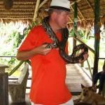 Tourist mit kleinen Anaconda auf den Schultern am Amazonas Kolumbiens bei Leticia